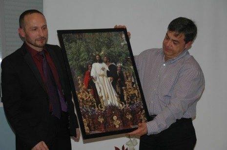 Rafael Garrigós hace entrega a Santiago Pérez,, representante de la Hermandad del Cristo, de un cuadro del Prendimiento de Sevilla